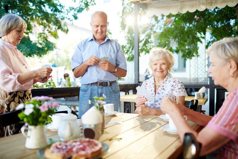 Карточки старшиев играя в кафе стоковая фотография