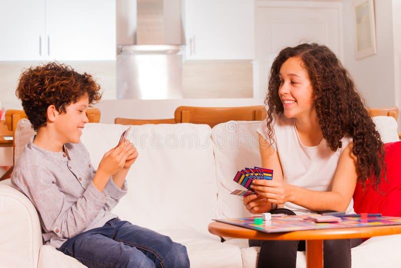 2 карточки счастливых друзей играя в живущей комнате стоковые фото
