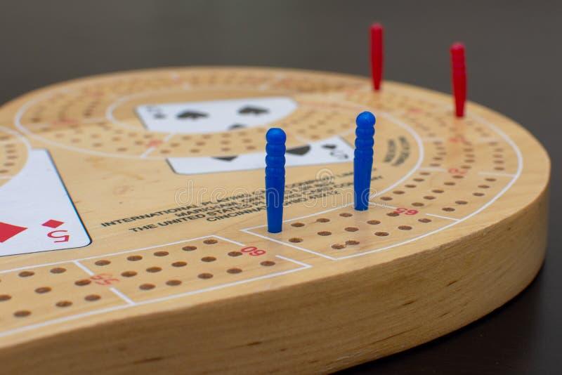 Карточная игра Cribbage и доски конец вверх смотря голубые и красные колышки стоковая фотография rf