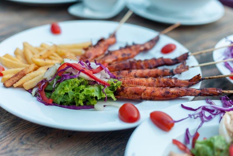 Картошка жарит с креветками фрая, салатом салата Над деревянной предпосылкой стоковые фотографии rf
