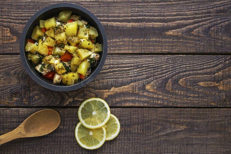 Картошки в баке на темном деревянном texrure с лимоном и ложкой покрывают стоковые фотографии rf