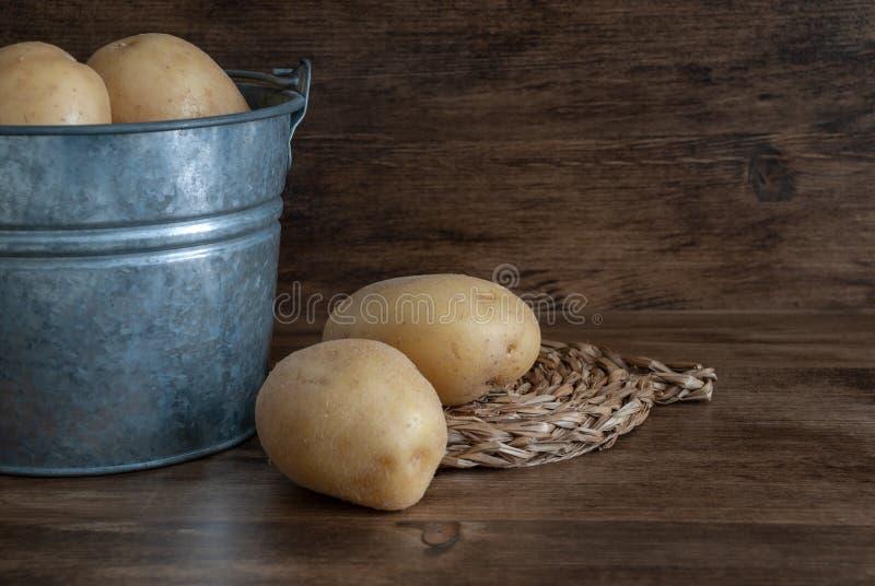 Картошки в ведре металла на темной деревянной предпосылке стоковые фотографии rf