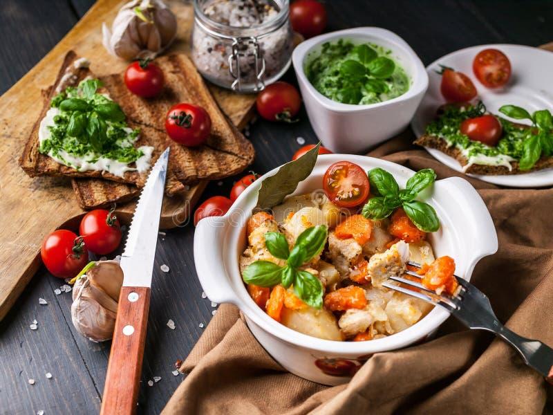 Картошки конца-вверх с цыпленком и овощами, сэндвичами с сыром и томатами вишни на темной деревянной предпосылке стоковое фото
