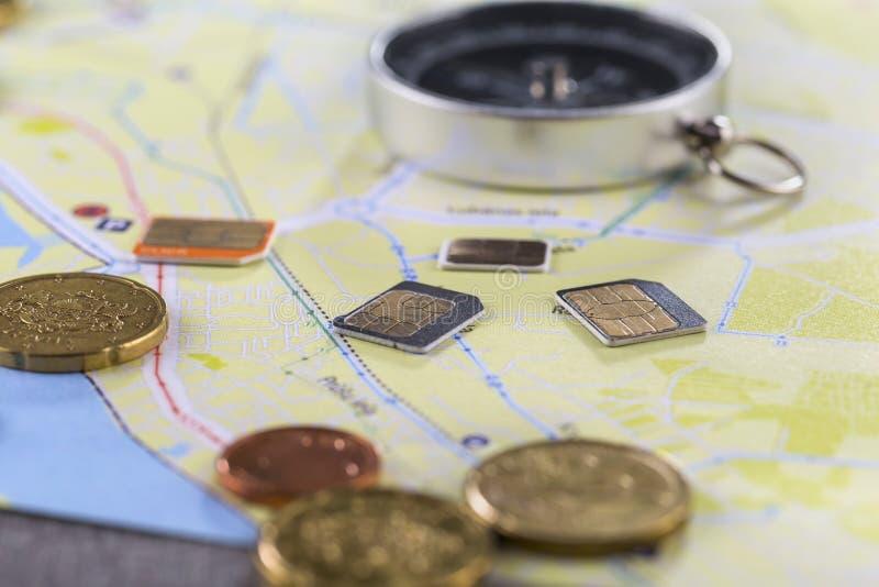 Карты gsm конца-вверх различных размеров лежат на карте города окруженной монетками, банкнотами евро и компасом стоковое фото