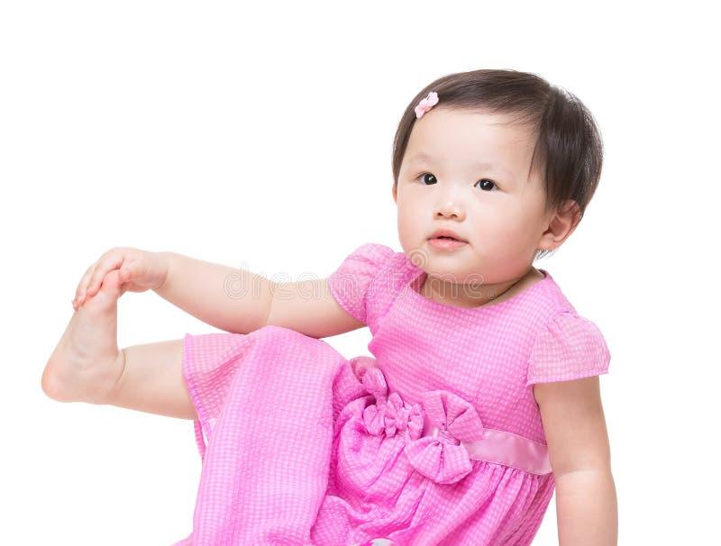 Касание маленькой девочки Азии ее ноги стоковые изображения