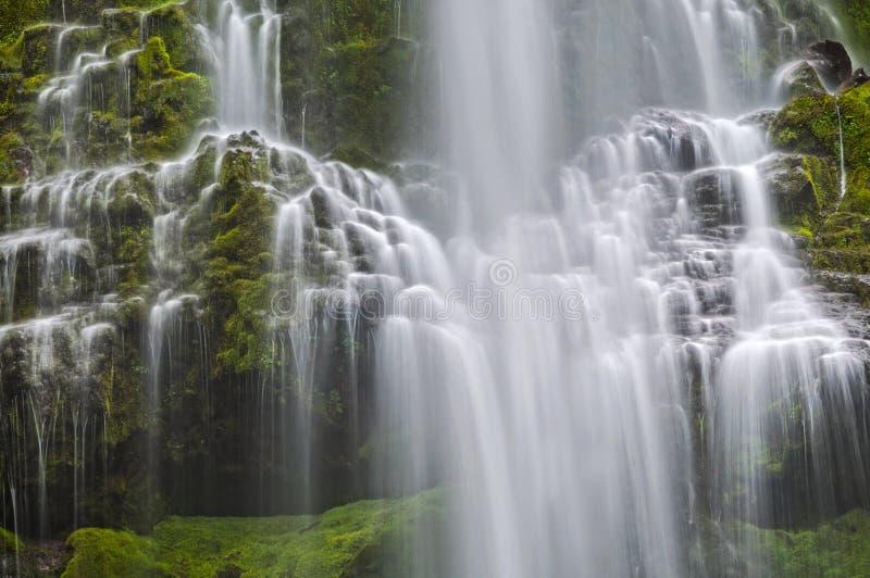 Каскадируя водопад со строками разлитой воды и зеленых мшистых утесов стоковые фото