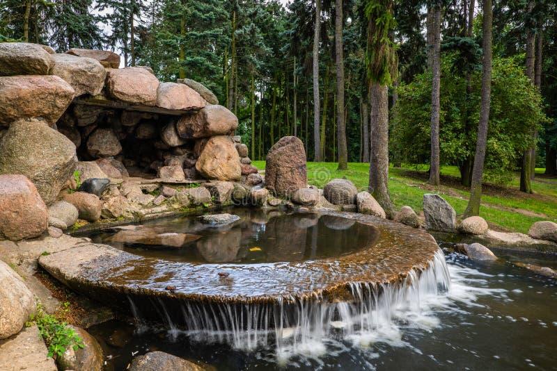 Каскад воды и небольшая пещера в парке стоковое изображение