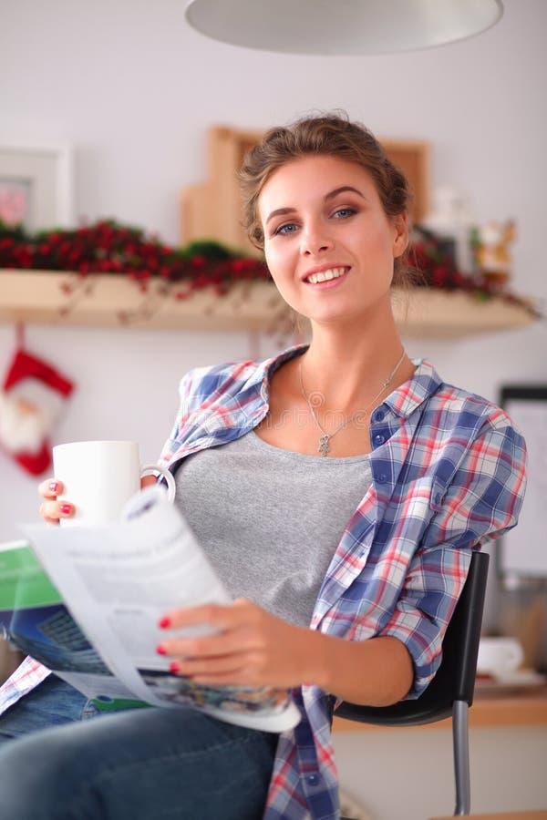 Кассета чтения женщины в кухне дома стоковое фото