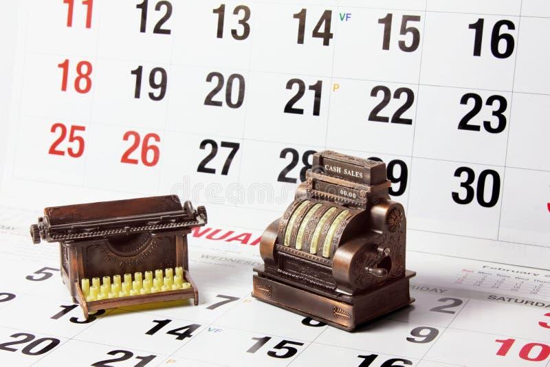Кассовый аппарат и машинка на страницах календара стоковая фотография rf