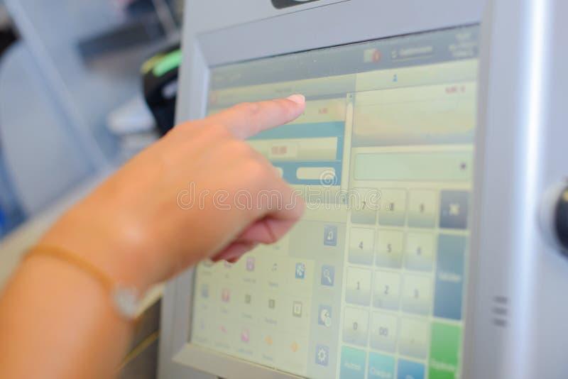 Кассовый аппарат экрана отжимать руки продавцев в магазине стоковые изображения rf