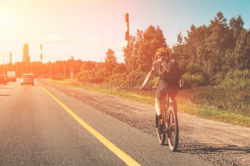 Катание велосипедиста на велосипеде на дороге асфальта сельской местности с автомобильным движением стоковая фотография