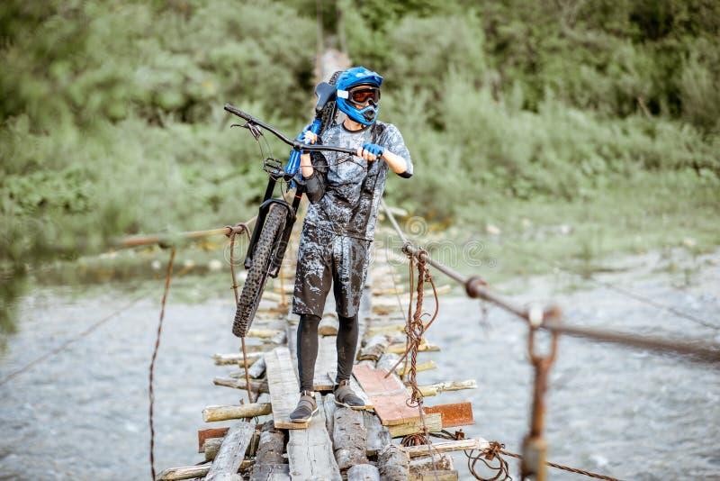 Катание велосипедиста на старом мосте в горах стоковое фото