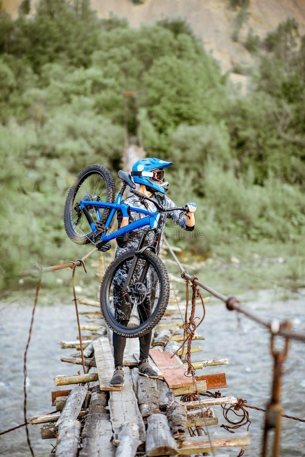 Катание велосипедиста на старом мосте в горах стоковое изображение
