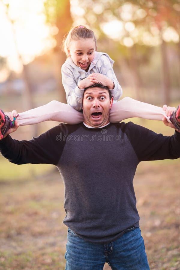 Катание девушки на плечах папы стоковая фотография rf