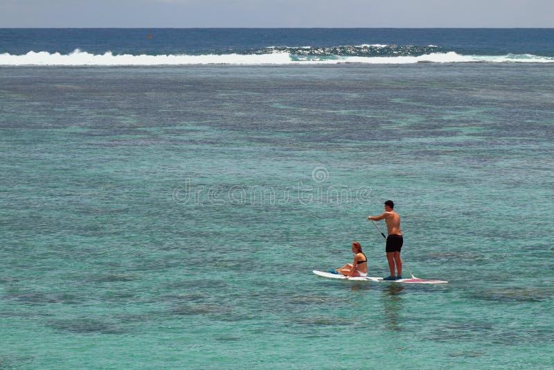 Катание девушки и молодого человека всходит на борт с веслом Обитель лагуны, реюньон стоковые фотографии rf
