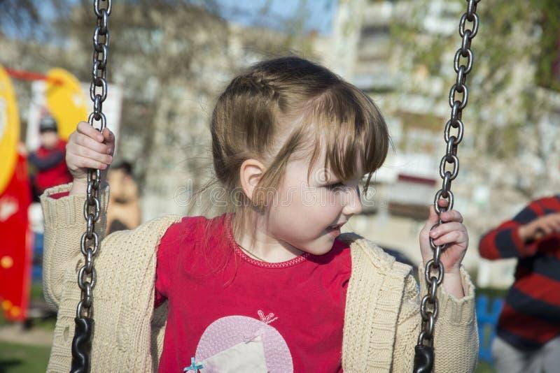 Катание маленькой девочки солнечного дня лета яркое на качании стоковое фото rf