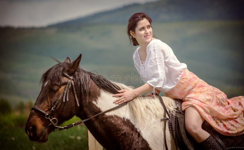 Катание молодой женщины на красивой лошади, имеющ потеху в временени, сельской местности Румынии стоковые фотографии rf