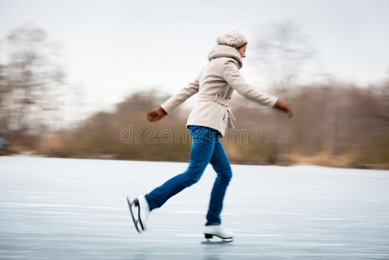 Катание на коньках молодой женщины outdoors на пруде стоковые изображения rf