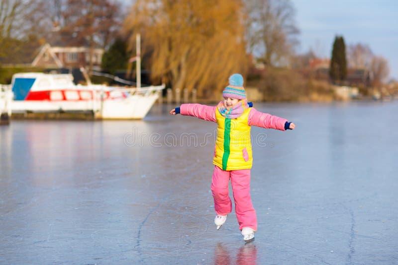Катание на коньках ребенка на замороженном канале мельницы в Голландии стоковое изображение rf