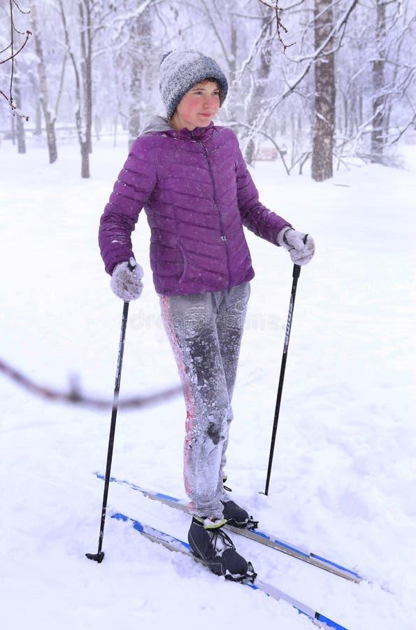 Катание на лыжах девушки подростка в парке в связанной куртке рассвета шляпы с лыжей стоковое фото