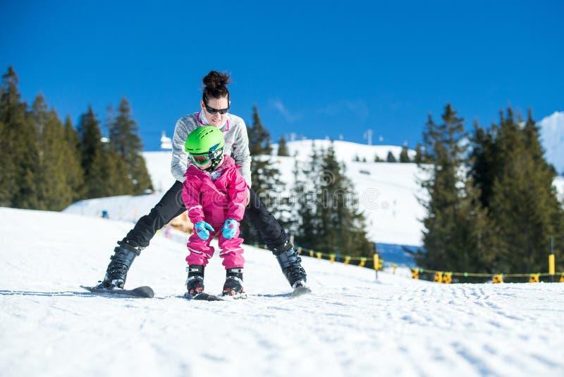 Катание на лыжах матери и маленького ребенка в горах Альпов Активные мама и малыш ягнятся с шлемом, изумлёнными взглядами и поляк стоковое изображение rf