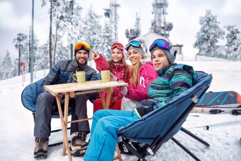 Катание на лыжах, потеха зимы - семья принимает перерыв на чай во время катания на лыжах на стоковое изображение rf