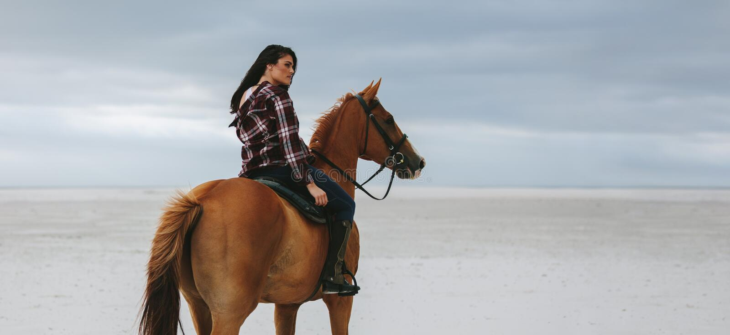 Катание пастушкы на лошади на пляже стоковые изображения