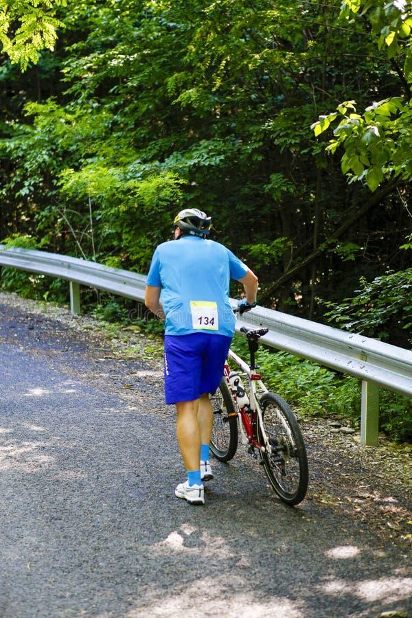 Катание старшего человека рядом с его велосипедом стоковое изображение