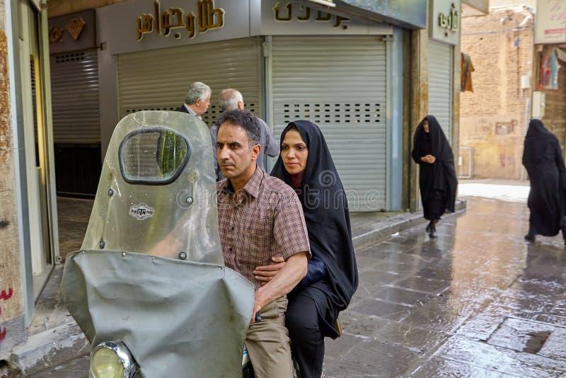 Катание супруга и жены на мотоцилк через улицы города, Иране стоковые изображения