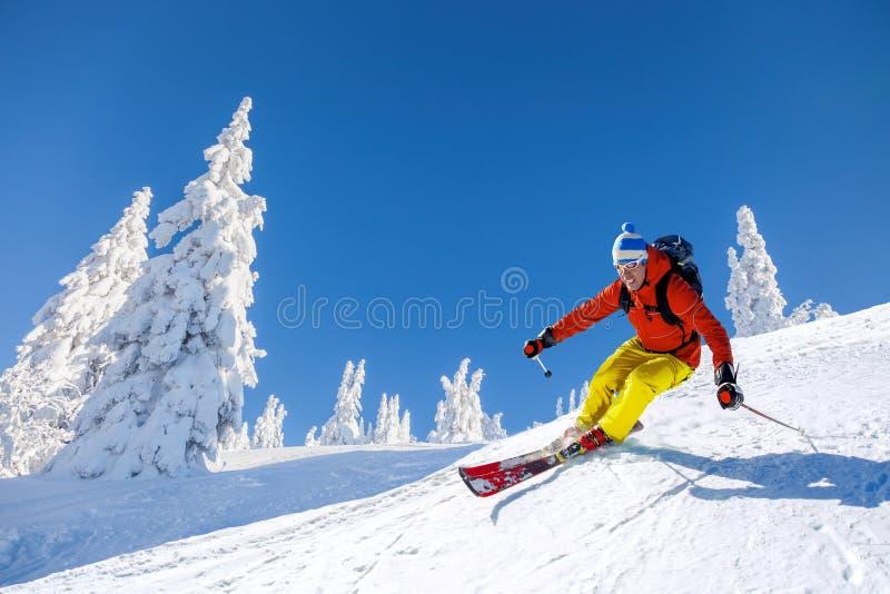 Кататься на лыжах лыжника покатый в высоких горах против голубого неба стоковые изображения rf