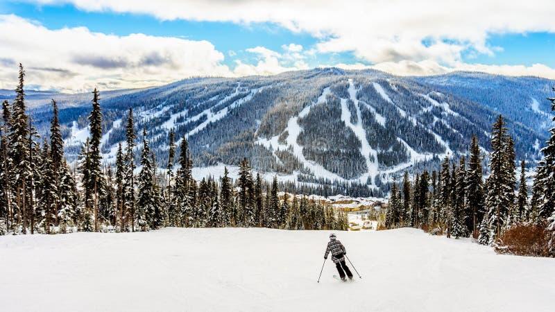 Кататься на лыжах вниз к деревне Солнця выступает стоковая фотография rf