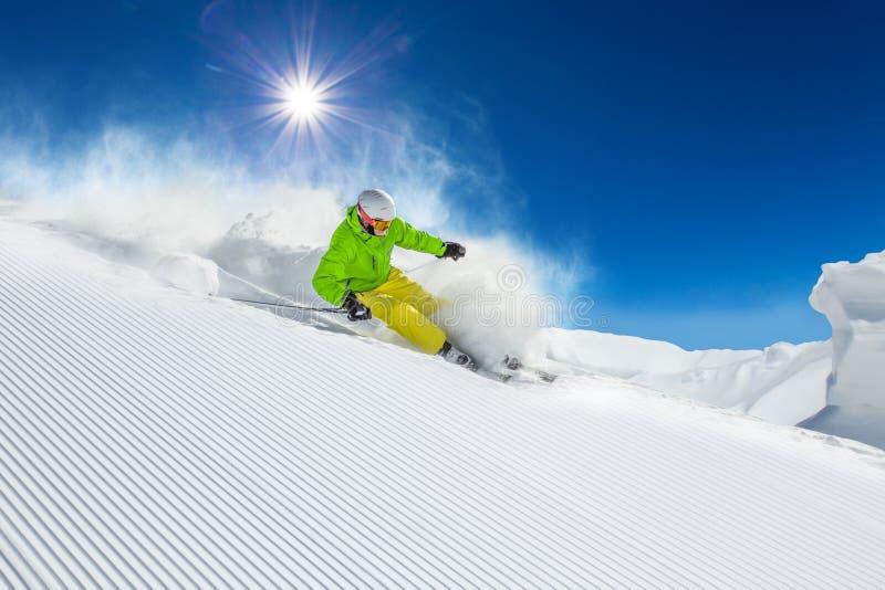 Кататься на лыжах лыжника покатый в высоких горах стоковое фото