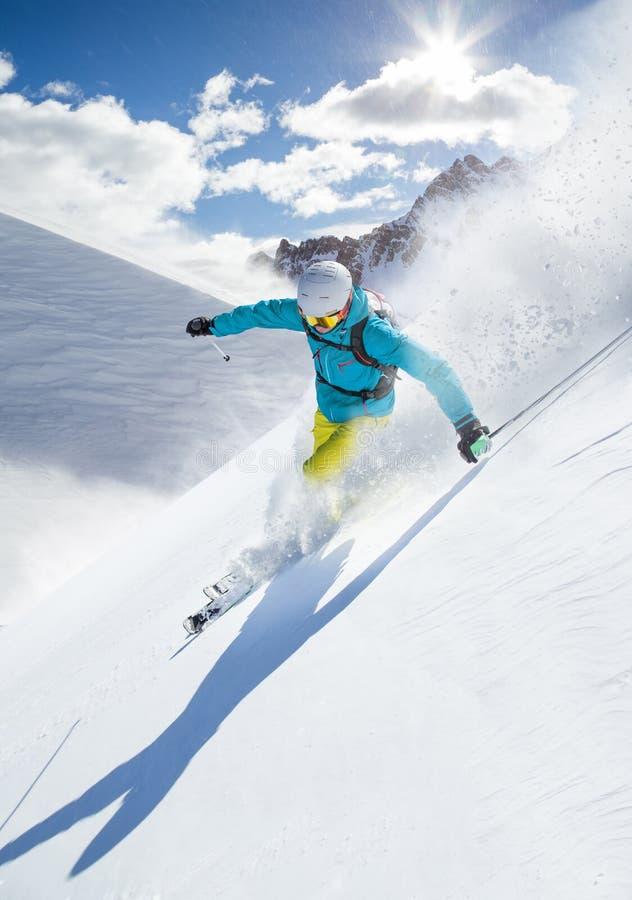 Кататься на лыжах лыжника покатый в высоких горах стоковые фотографии rf
