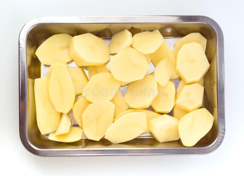 Катит сырцовую картошку на подносе выпечки стоковая фотография