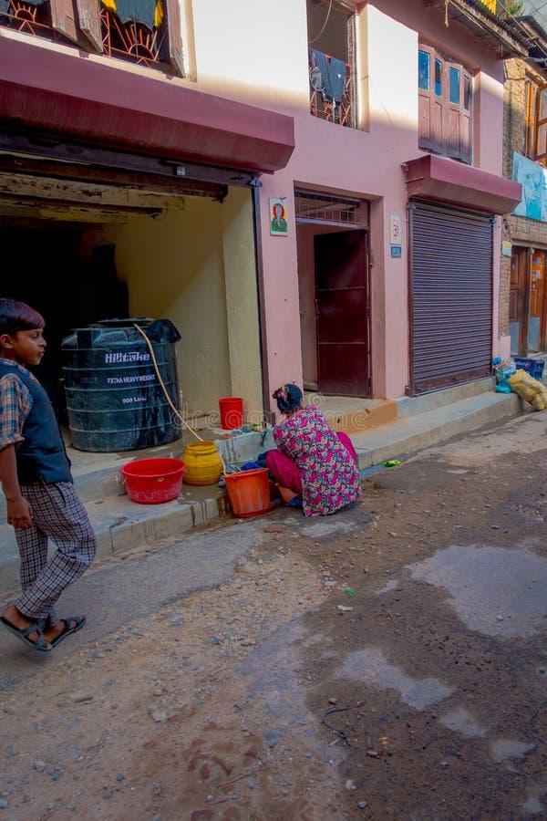 КАТМАНДУ, НЕПАЛ 15-ОЕ ОКТЯБРЯ 2017: Неопознанный ребенок идя в улицы и одежды женщины моя в улицах внутри стоковое изображение rf