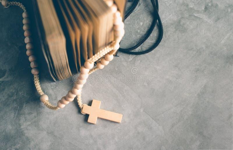 Католический розарий отбортовывает с старой книгой на молитве таблицы цемента, rosa стоковое изображение