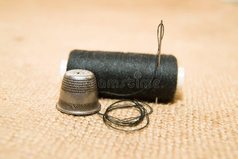 Катышка иглы, кольца и потока на старой ткани стоковые фотографии rf