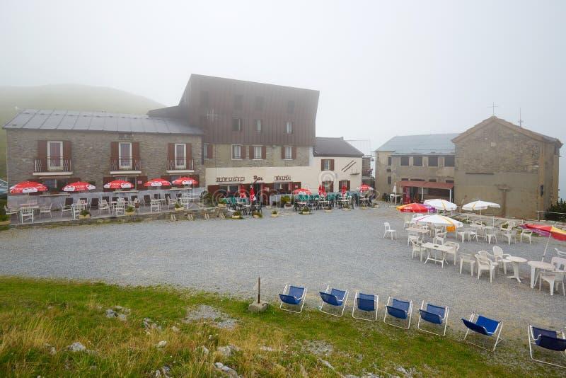 Кафе хижины Balma с на открытом воздухе таблицами и стульями в туманном летнем дне в Prato Nevoso, Италии стоковая фотография