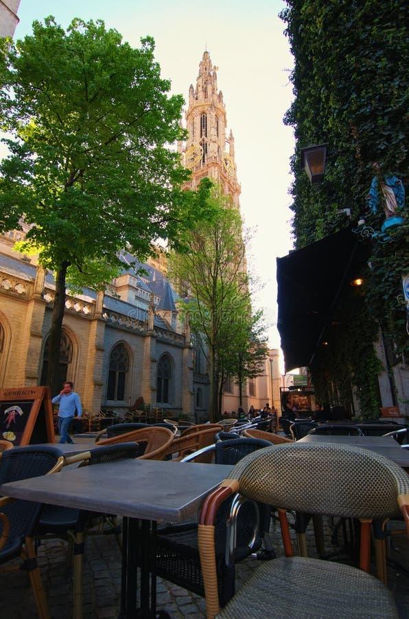 Кафе Ozy в тихой улице с живописным взглядом к башне собора нашей дамы Голландск: Onze-Lieve-Vrouwekathedraal стоковые изображения rf