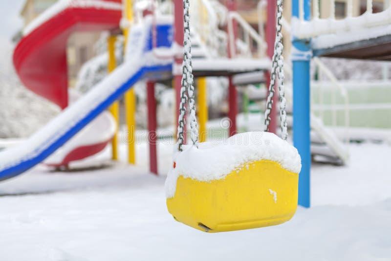 Качание и скольжение покрытые снегом на спортивной площадке в зиме стоковые фото