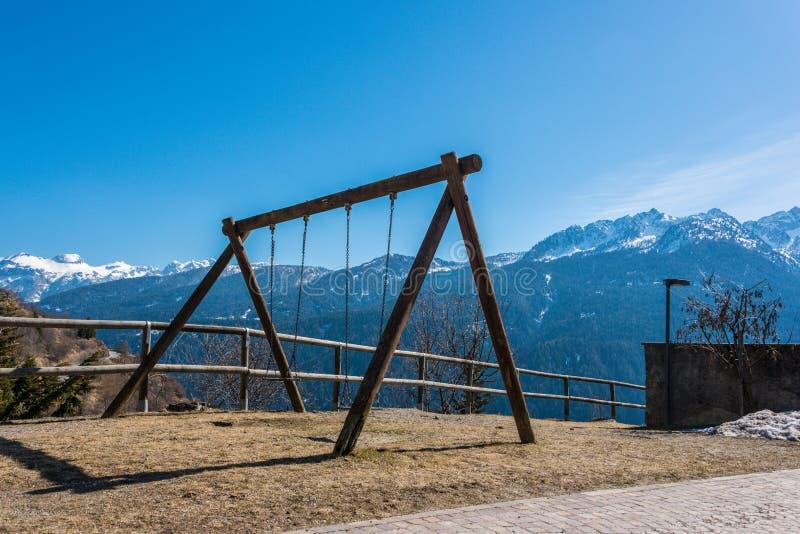 Качание, спортивная площадка ребенка, горный вид, снег покрыло горы Альп стоковая фотография