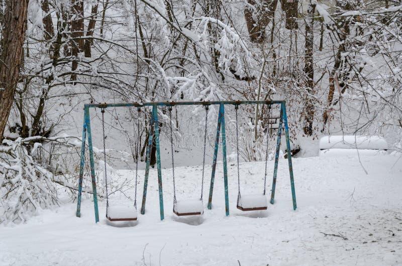 Качания в детей покрытых спортивной площадке снегом стоковое изображение