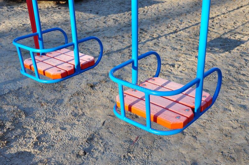 Качания металла красочные с деревянным местом на игровой площадке стоковые фотографии rf