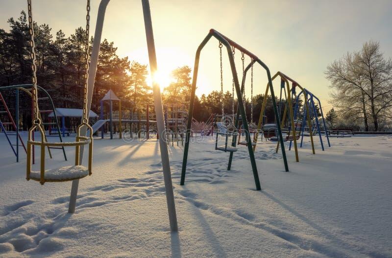 Качания на спортивной площадке покрытой с снегом в зимнем времени стоковое изображение