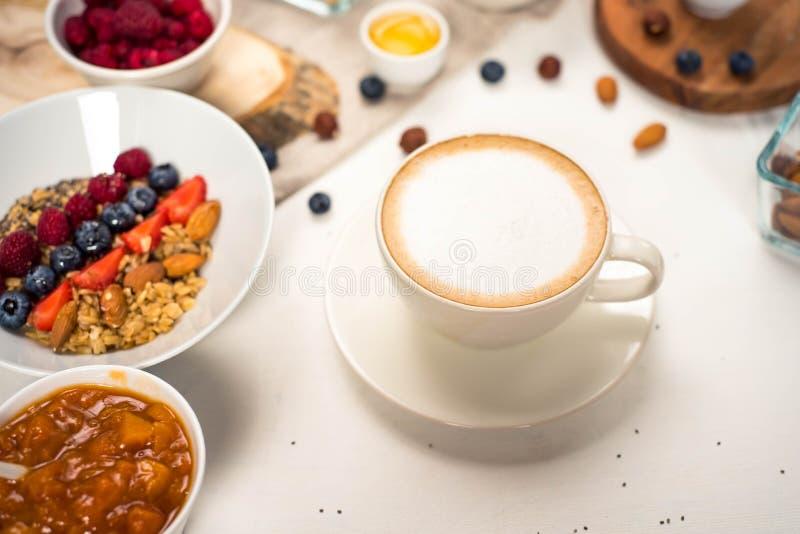 Каша квиноа завтрака с свежими фруктами в предпосылке завтрака шара здоровой с кофе, ягодами, яичком, гайками стоковые фотографии rf