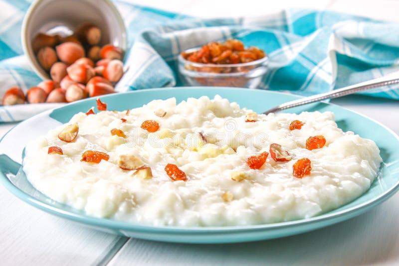 Каша молока риса с гайками и изюминками в голубом блюде на белом деревянном столе стоковые изображения rf