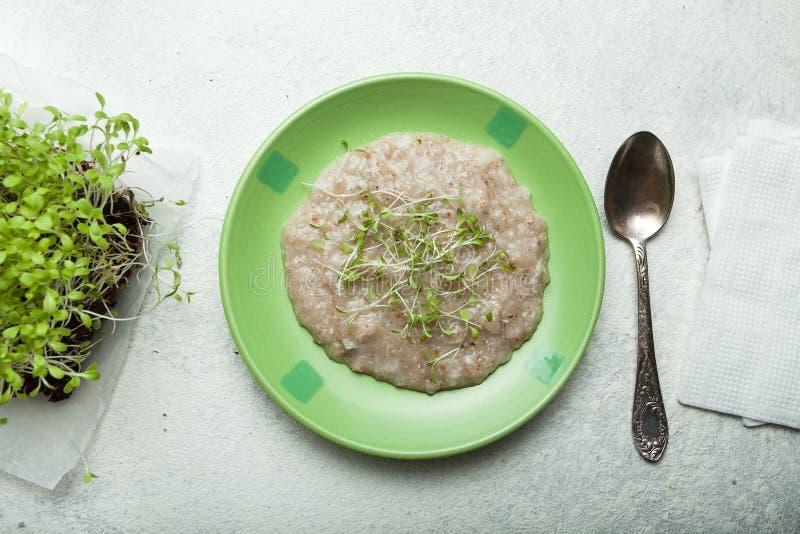 Каша овса с микро-зеленым на плите Здоровый питательный завтрак для того чтобы улучшить функцию мозга r стоковое фото rf
