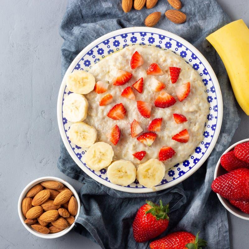 Каша овсяной каши с клубниками, бананом и миндалинами Здоровый завтрак со свежими органическими ягодами стоковое фото rf