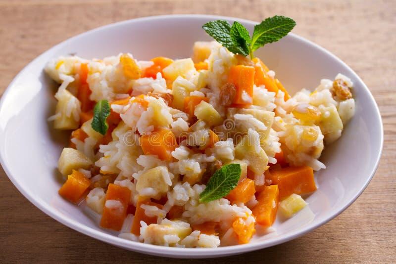 Каша риса с тыквой, яблоками и изюминками в белом шаре Вегетарианское блюдо диеты риса и тыквы еда здоровая стоковые изображения rf
