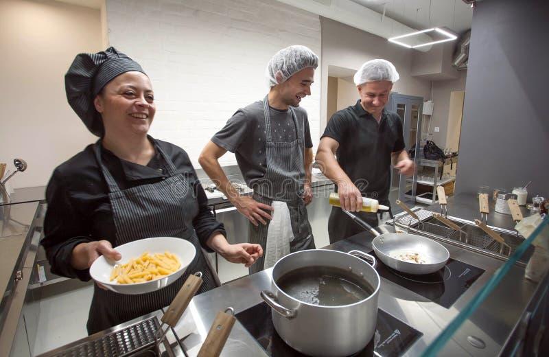 Кашевары и шеф-повар варя итальянские макаронные изделия еды и усмехаясь на открытой кухне внутри современного ресторана стоковое фото rf